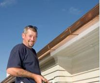 photo of roofer near the roof top of home serviced by Mulligan Windows, Siding and Roofing in Farmington, MI