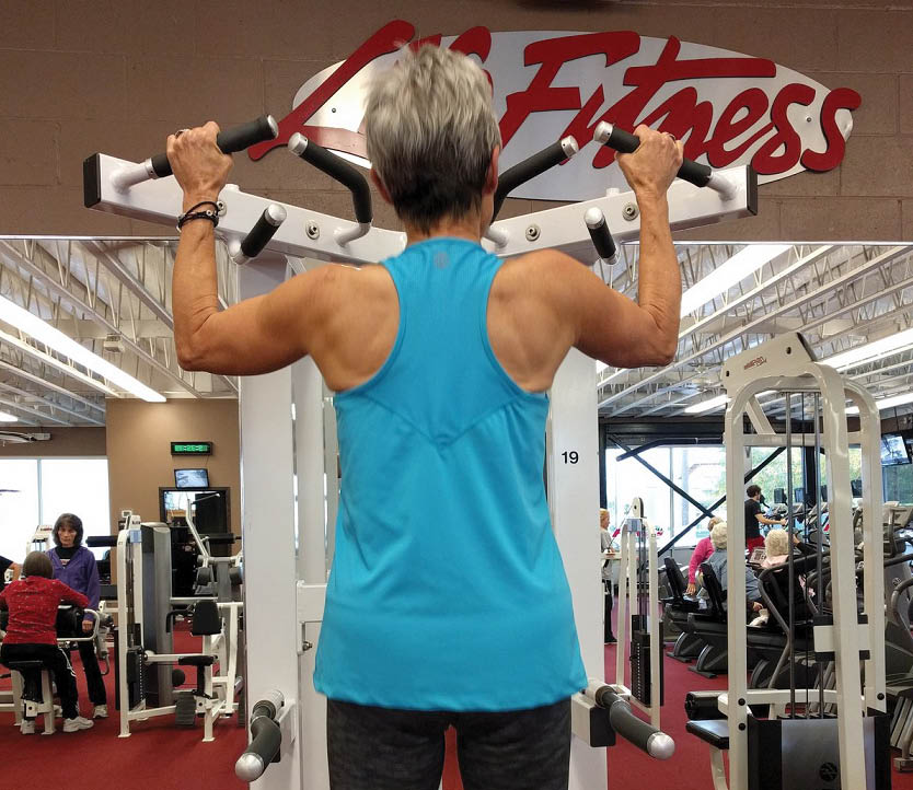 Woman working out on a fitness machine at North Hill Fitness in Edgewood, WA - weight machines - fitness clubs near me - health clubs near me - gyms near me - fitness club coupons - health club coupons