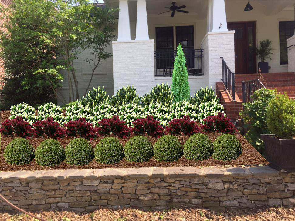 Stone wall and backdrop of landscaping with shrubs, plants and mulch