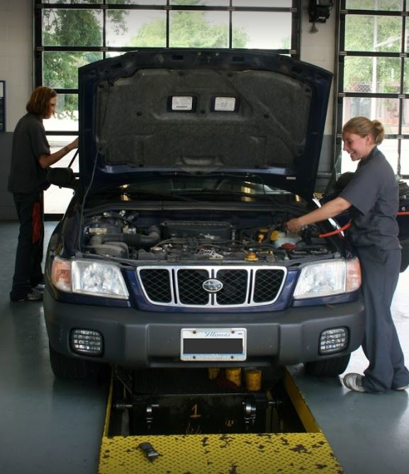 OTC auto technician performing an oil change in the service bay