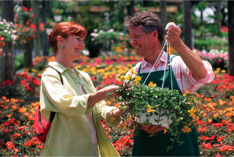 Woman shopping for hanging flower basket.