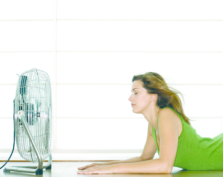 Woman laying in front of fan.