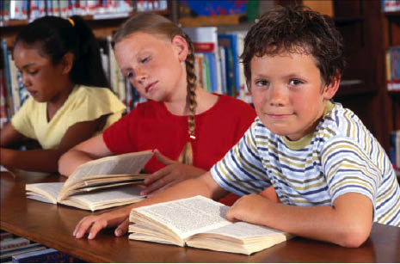 three children sitting in school with open books