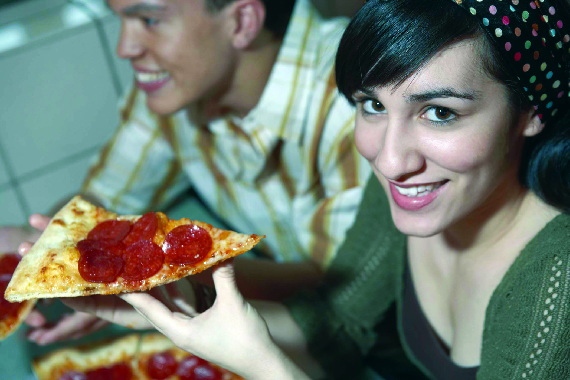 Picture of woman eating pizza from Andreas Italian restaurant.