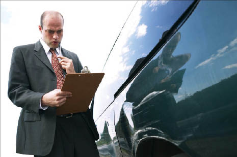 automotive insurance claims adjuster looking at car damage. Palm Springs auto body repair work