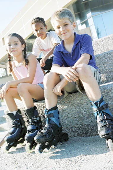 Kids with rollerblades sitting on concrete stairs.