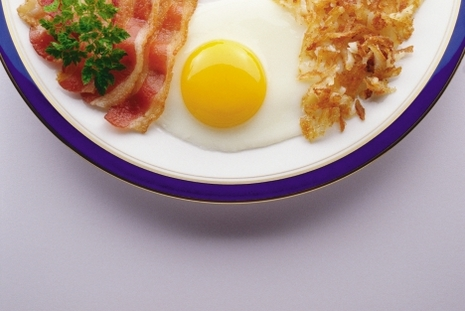 Breakfast plate of egg, bacon and hashbrowns.