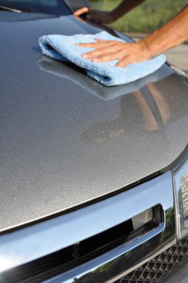 Attendant polishes car with shine cloth