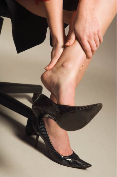 Photo of woman rubbing her Achilles tendon wearing high heels. Let Dr. Anthony Perez treat your foot pain caused by daily wear and tear.