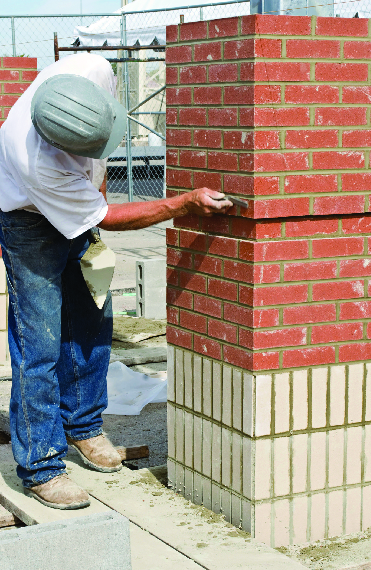 Masonry worker repairing chimney.