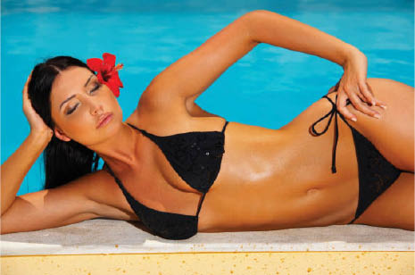 (girl in black bikini lying by pool) Save on spray tanning with our tanning coupons