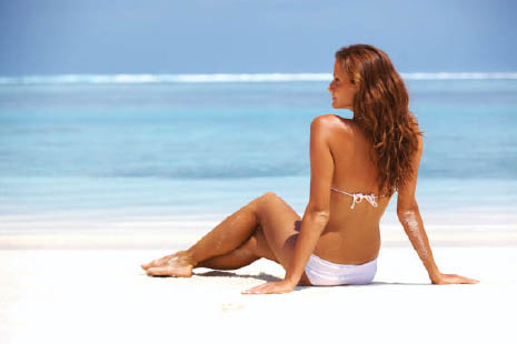 tan woman on the beach; build up a beach-worthy base tan with our tanning beds in Franklin, WI