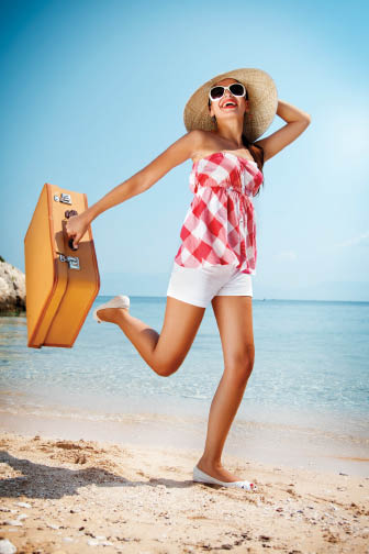 Woman on the beach holding suitcase and sun hat.