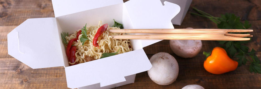 Chinese food to go box with veggies and chopsticks banner