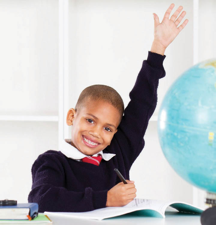 eager young child raising his hand in class