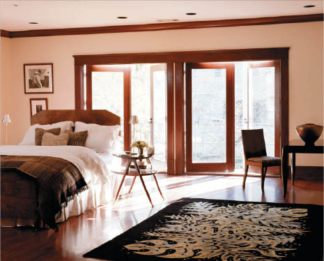 bedroom with natural light shining through windows & doors
