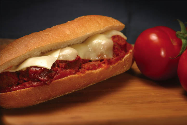 Meatball sandwich covered in marinara and mozzarella cheese.