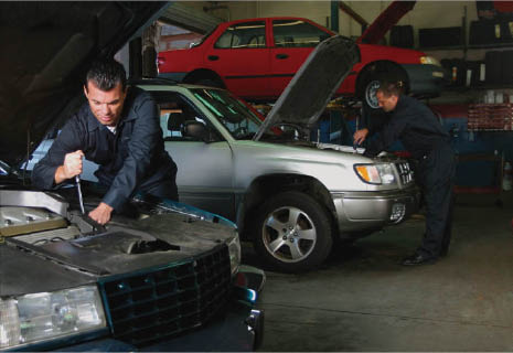 two auto technicians working on two different cars in a garage