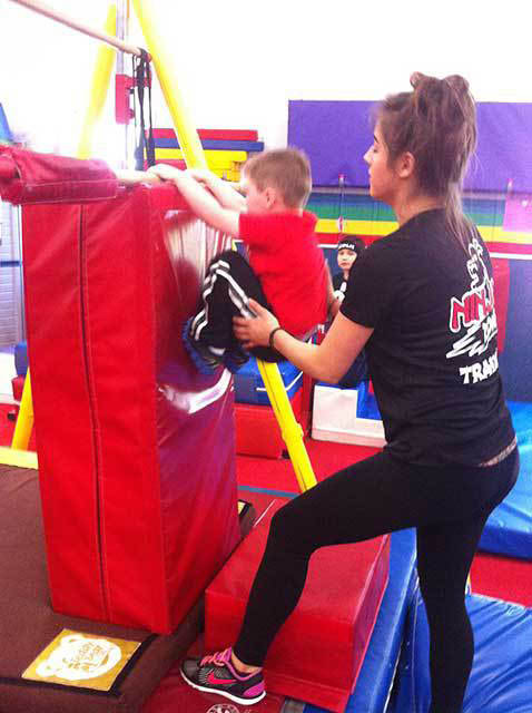 Young boy scaling wall at Ninja Zone class.