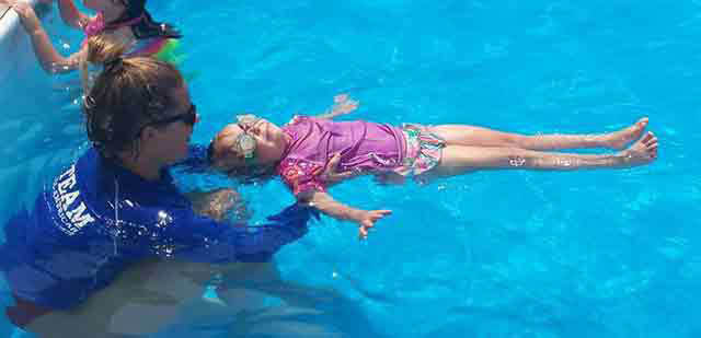 Swim instructor and young girl floating on her back.