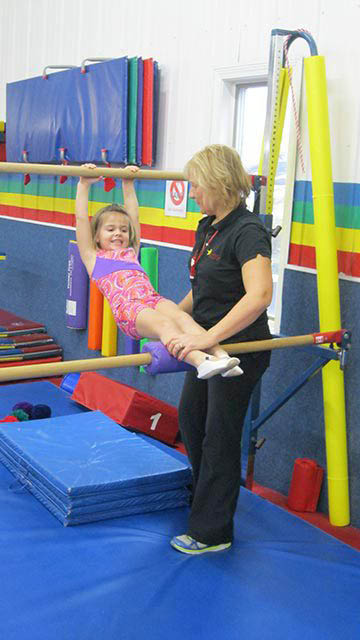 Young girl and instructor on parallel bars.