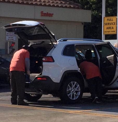 white SUV being cleaned by car wash techs