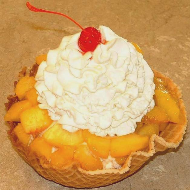 Peach sundae in a waffle bowl with whipped cream