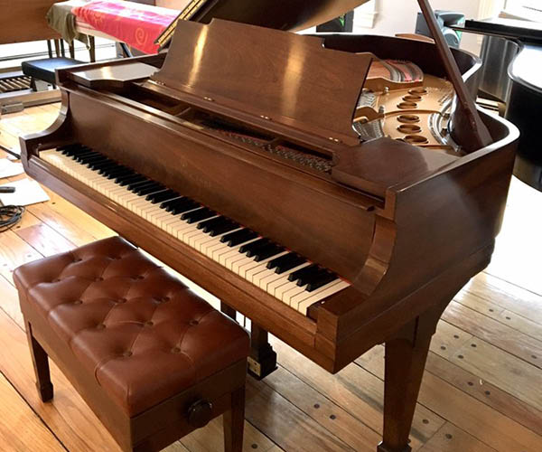 brown piano with leather seat