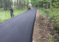 New asphalt-paved long driveway through woods by Rocky Top Asphalt Paving in Nashville, TN