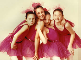 four young girls in dance outfits