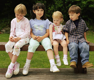 four young kids sitting on bench