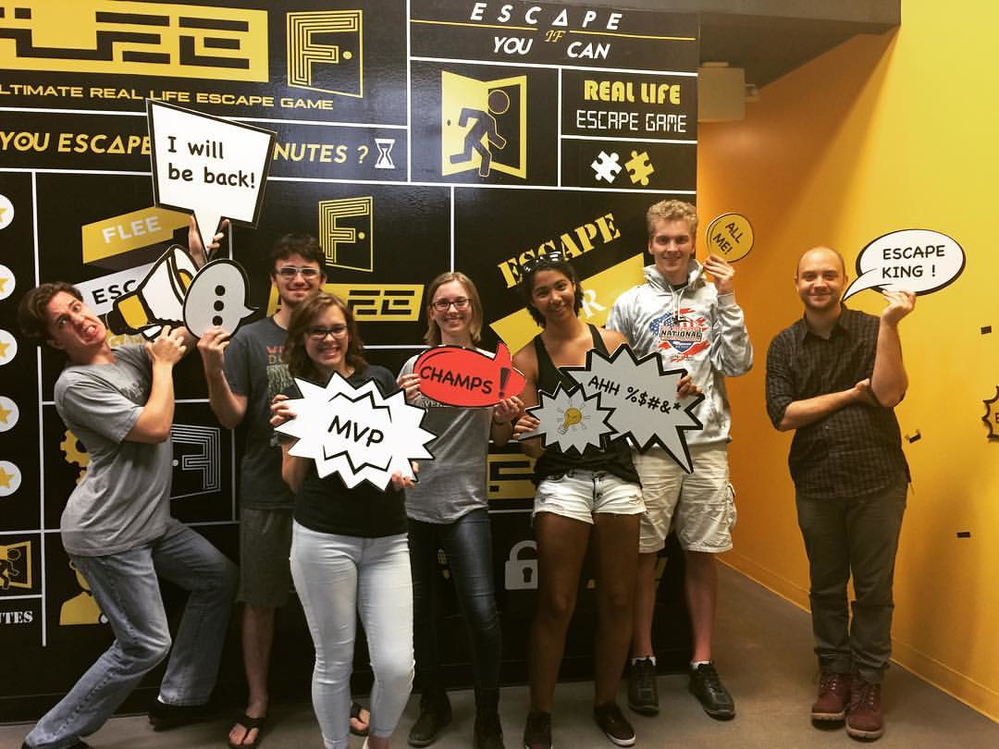 Friends having fun working as a team at Flee Escape Room in Seattle, WA and Redmond, WA - Entertainment and Recreation