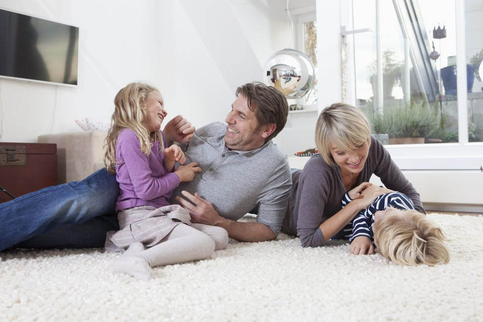 Happy family sitting on their clean carpet cleaned by Snohomish Carpet Cleaning - Snohomish, WA