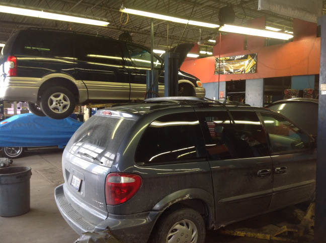 SUV in auto service bay; Speedy Auto Service, Westland, MI; oil change coupon; brakes service