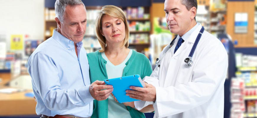 Pharmacist and customers reviewing a prescription at Syd's Pharmacy