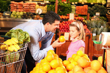 Man and daughter eating oranges at Tom's Farms produce market