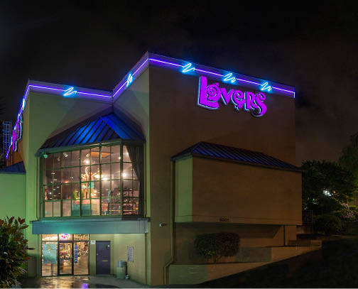 Nighttime shot of two-story Lovers Package adult novelty store in Washington and Oregon