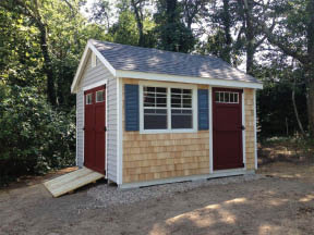 This yard shed has lights in the doors which is a good way to get natural light into a shed. Also notice the natural white cedar shingle siding which matches the homes exterior.