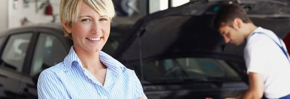 photo of smiling woman in front of auto mechanic from Tim's Complete Auto Maintenance in Utica, MI