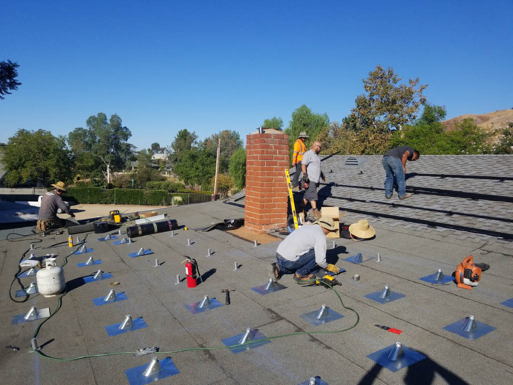 Technicians installing solar panels on the roof of a house - Jeremy's Electric - heat with solar power - Tujunga, CA