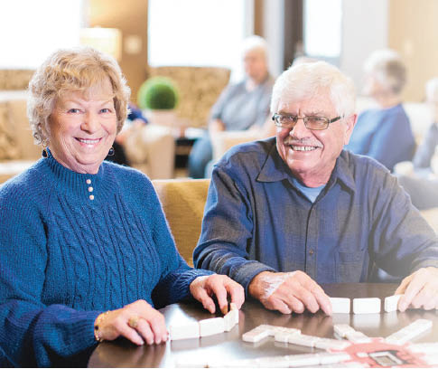 A couple having fun playing dominoes at Village Concepts of Gig Harbor - Sound Vista Village - retirement communities in Auburn - retirement communities near me