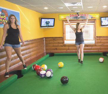 photo of girls on the life size pool table at Wild Woody's in Shelby Township, MI