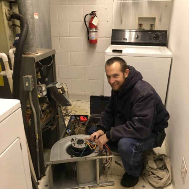 HVAC specialist inspecting and cleaning a faulty furnace