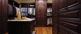 Man's closet with all dark wood finishes and shelves; Artisan Custom Closets, Georgia