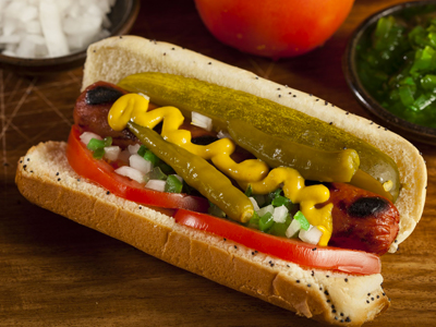 Classic mustard, onion sport pepper on a hot dog.