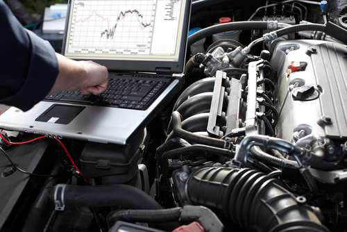 Automotive repair technicians monitoring engine performance