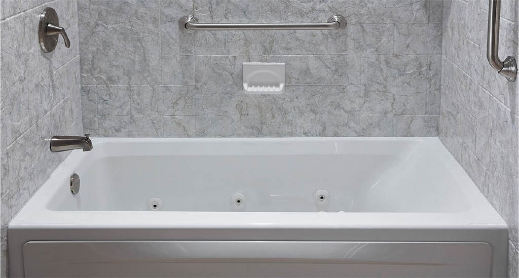 White bathtub and surround with safety bars.