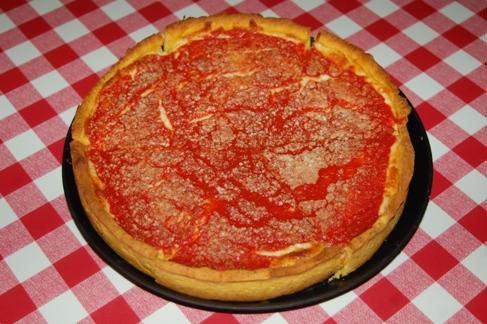 Picture of Beggar's Pizza deep dish pizza on red and white checkered tablecloth.