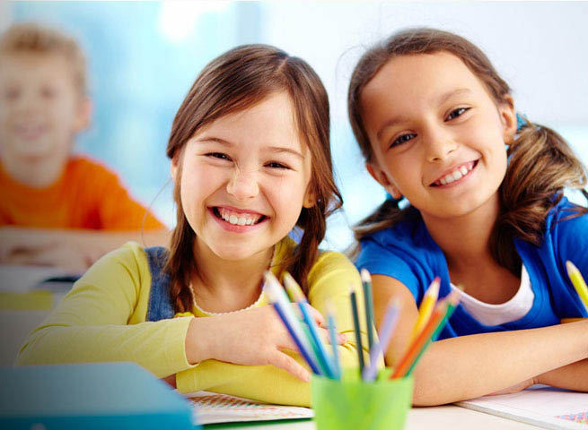 Two girls smiling sitting in a classroom with color pencils and a boy student in the background.