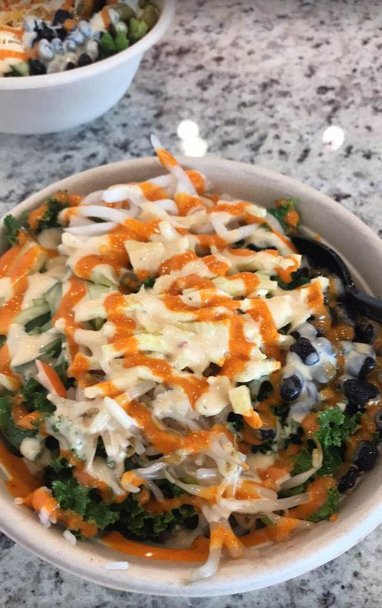 Asian bistro bowl topped with sriracha with kale and beans